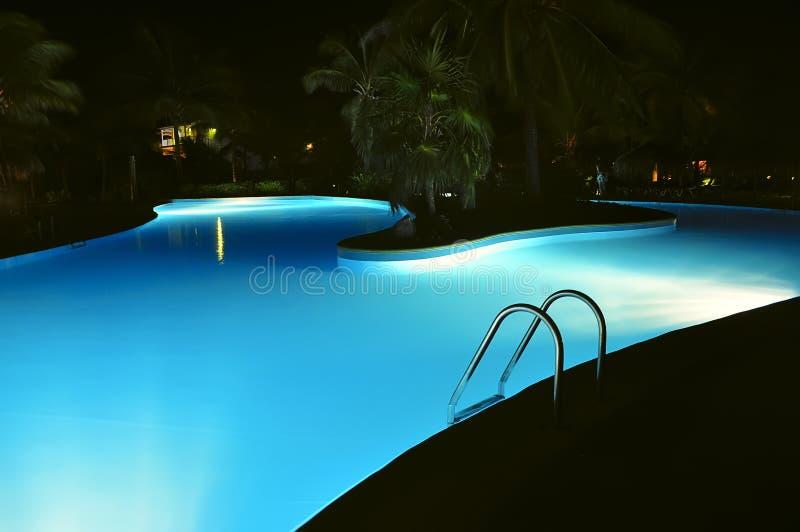 Nacht zwembad met verlichting stock afbeelding
