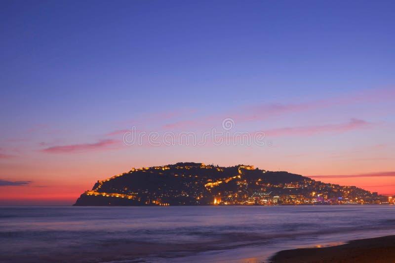 Nachtansicht des Berges das Alanya, die Türkei blaues Mittelmeer, rosa Sonnenuntergang, Berg von Alanya glänzt Nachtlichter stockfotos