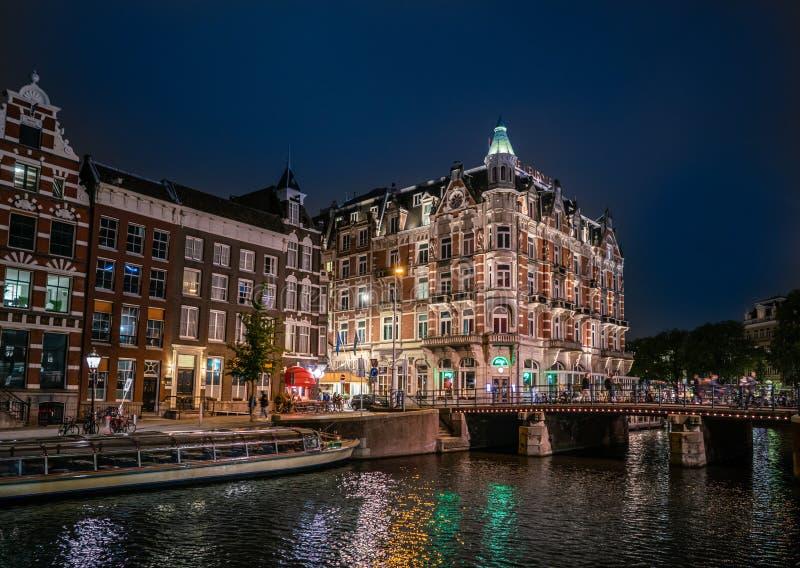Nachtansicht des Hotels L Europa mit fünf Sternen an der Ecke des Rokin und des Amstel-Flusses stockfotografie