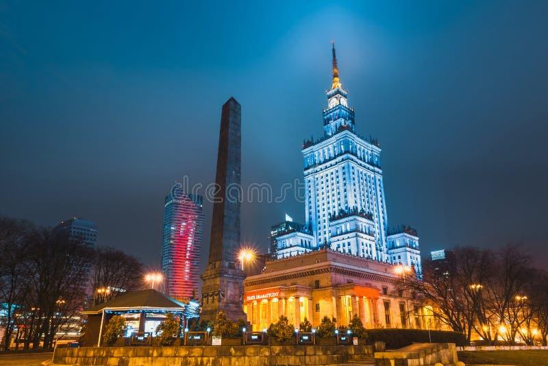 Nachtansicht des Palastes der Kultur und der Wissenschaft und in die Stadt mit Geschäftswolkenkratzern lizenzfreies stockbild