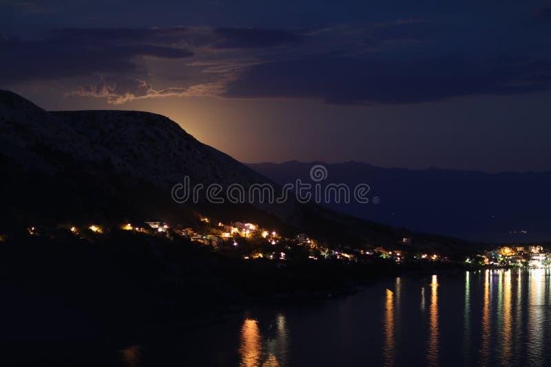 Nachtansicht mit Mondlicht auf die Stadt auf einem Ufer von adriatischem Meer vom Felshügel in Kroatien, verschiedene Farbtöne stockfotos