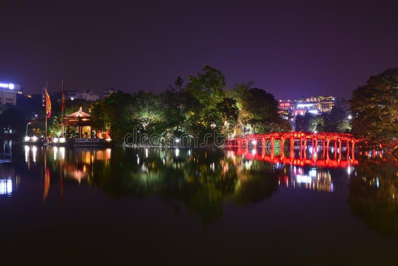 Nachtansicht mit Wasserreflexion der Huc-Brücke im hellen Rot mit Ngoc-Sohn-Tempel, Hanoi, Vietnam lizenzfreies stockfoto