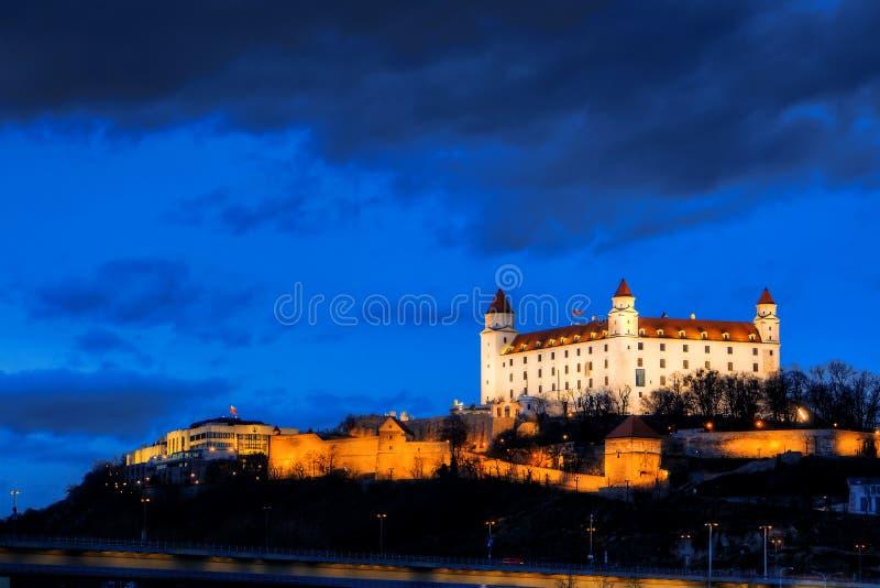 Nachtansicht von Bratislava-Schloss von der Flussoberfläche mit drastischen Sonnenuntergangskylinen lizenzfreies stockbild