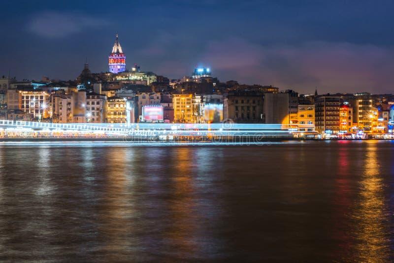 Nachtansicht von Istanbul-Stadtbild Galata-Turm mit dem Schwimmen von touristischen Booten in Bosphorus, Istanbul die Türkei stockfotografie