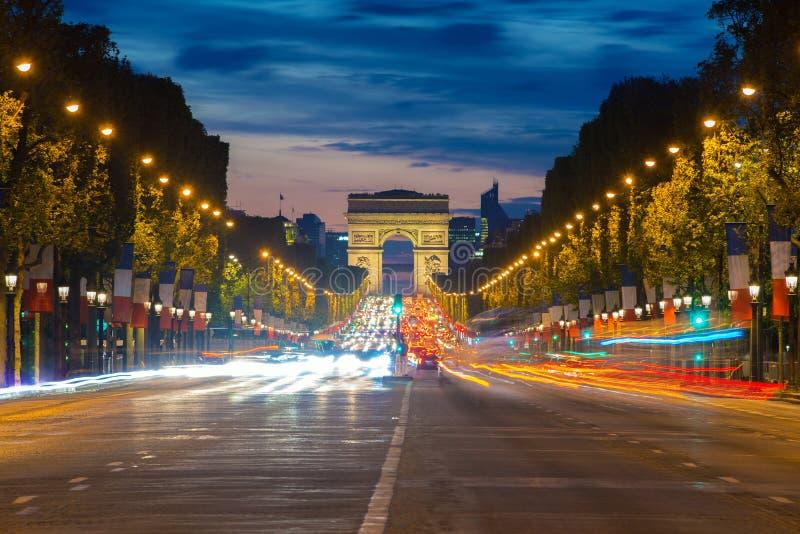 Nachtansicht von Paris-Verkehr in Champs-Elyseesstraße und im Bogen lizenzfreie stockfotos
