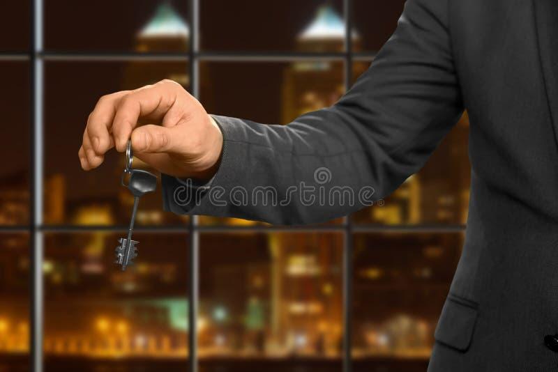 Nachtbüroangestellter, der Schlüssel hält stockfotografie