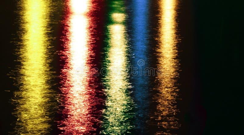Nachtbunter Auszug beleuchtet Reflexionen auf See stockbild