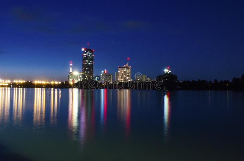 Nachtcityscape in de rivieroever van Wenen met kleurrijke lichten en multi storied de bouwbezinning van water stock foto