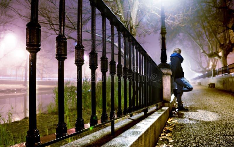 nachtcityscape en eenzame mens stock foto