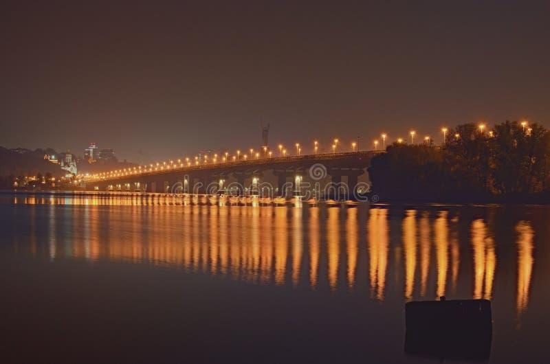 Nachtcityscape met Paton-brug over Dnieper-rivier Het monument van het vaderland bij de achtergrond Stadslichten in het water wor royalty-vrije stock afbeeldingen