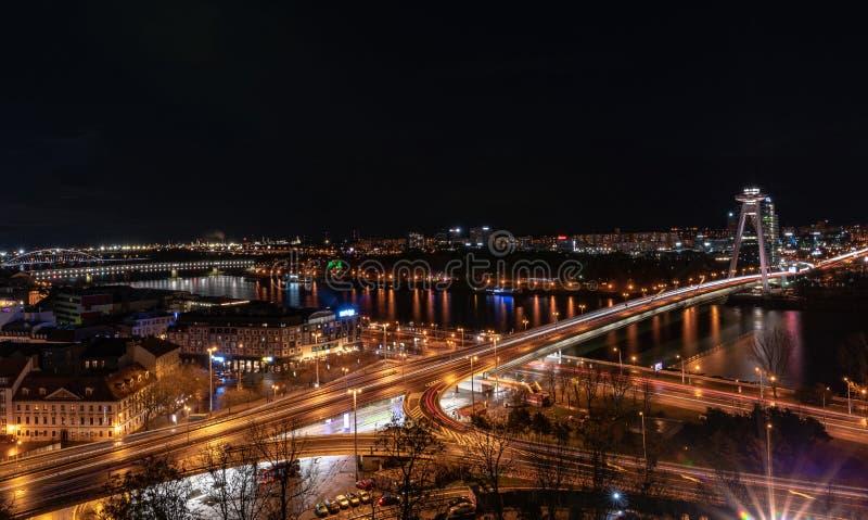 Nachtcityscape van het kapitaal van Slowakije, Bratislava over de rivier van Donau stock fotografie
