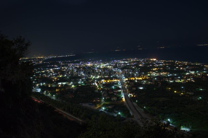 Nachtfoto einer Stadt von der Spitze eines Hügels stockfotos