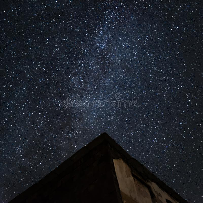 Nachthemel en de Melkweg over oud verlaten huis royalty-vrije stock afbeelding