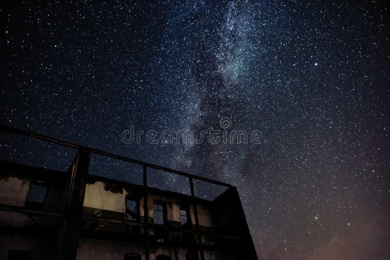 Nachthemel en de Melkweg over oud verlaten huis royalty-vrije stock foto's