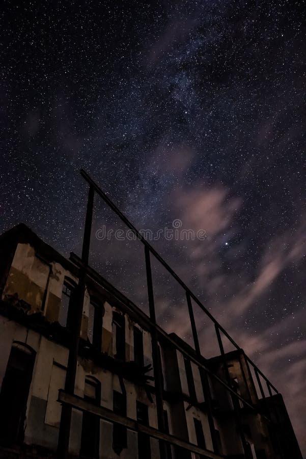 Nachthemel en de Melkweg over oud verlaten huis stock fotografie