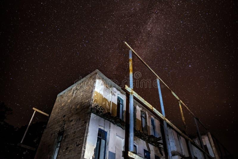 Nachthemel en de Melkweg over oud verlaten huis stock foto