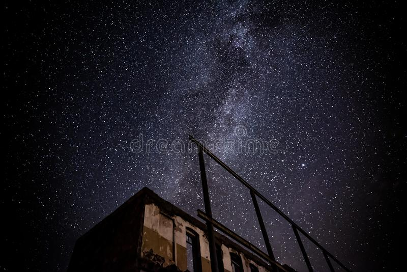 Nachthemel en de Melkweg over oud verlaten huis royalty-vrije stock foto