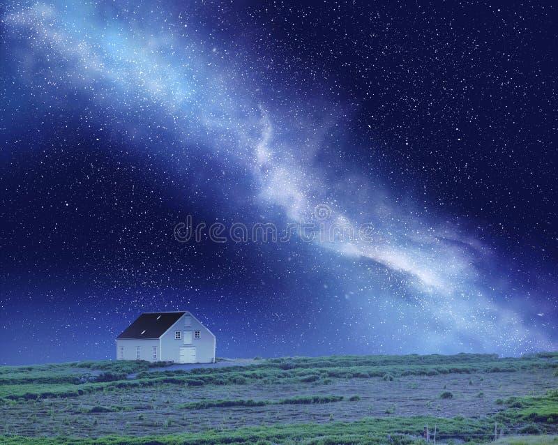 Nachthemel met melkachtig manier en huis stock foto's
