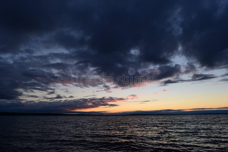 Nachthemel met schemeringgloed in de wolken boven de donkere golven van het meerwater royalty-vrije stock afbeelding