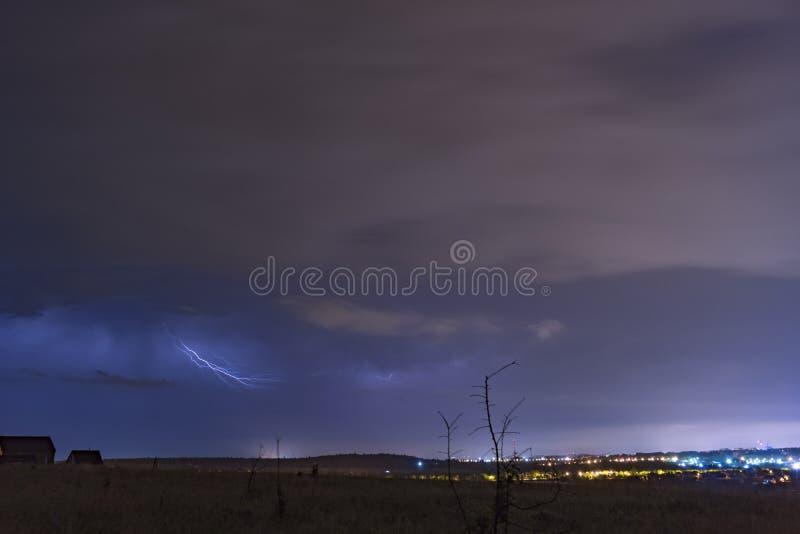 Nachthemel met wolken en bliksem over een kleine stad royalty-vrije stock fotografie