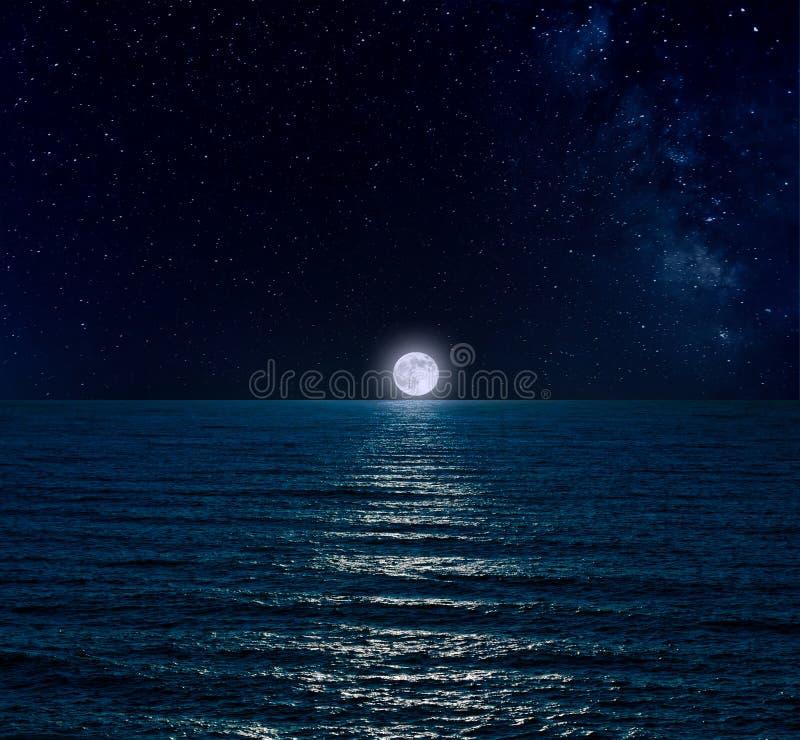 Nachthemel over overzees met volle maan stock fotografie