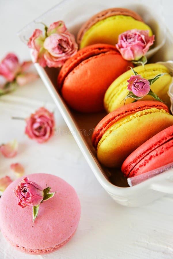 Nachtisch: Blüht empfindliche frische bunte französische Makronen in der Pastellfarbgeschenkbox Rosen auf hellem Textilhintergrun stockbild