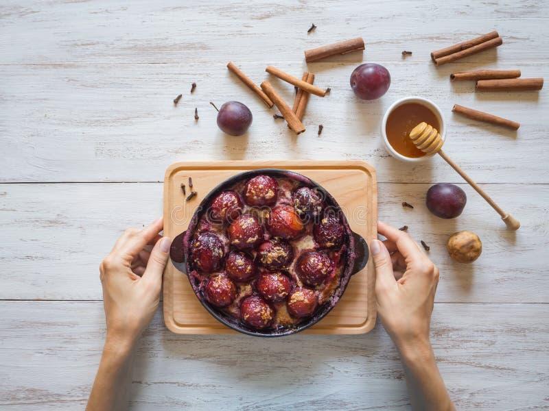 Nachtisch der gebackenen Pflaume in einer Wanne mit Nelken, Zimt, Honig und Eifer lizenzfreies stockfoto