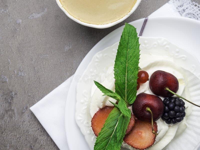 Nachtisch pavlova Meringe mit Schlagsahne und tadellose Blattdekoration und -Tasse Kaffee stockfotografie