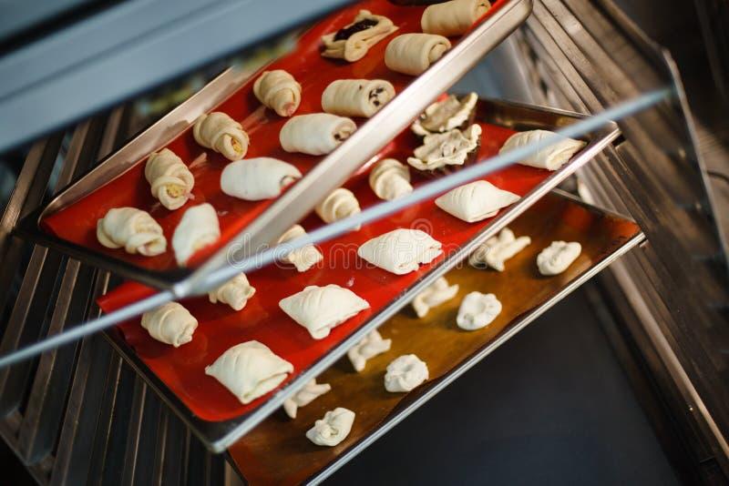 Nachtischbacken auf Backblechen im Ofen lizenzfreie stockbilder