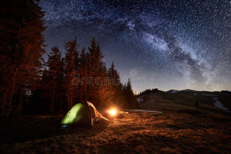 Nachtkampieren Belichtetes Zelt und Lagerfeuer nahe Wald unter nächtlichem Himmel voll von Sternen und von Milchstraße lizenzfreies stockfoto