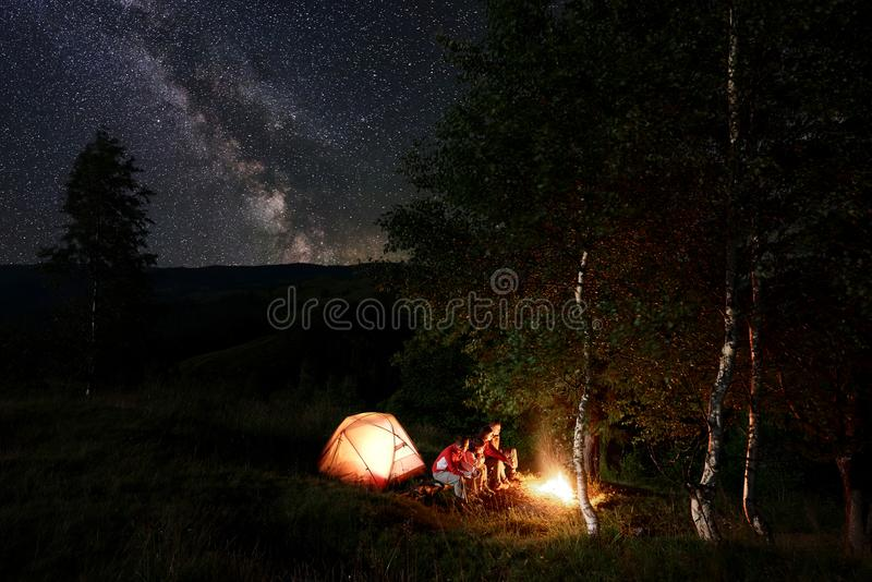 Nachtkampieren Freunde durch das Lagerfeuer, das auf Klotz unter Bäumen sitzt, nähern sich Zelt unter sternenklarem Himmel stockfoto