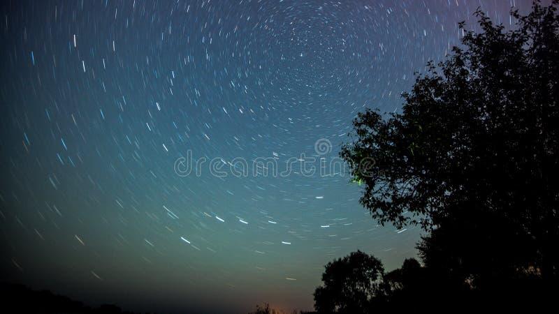 Nachtlandschap met kleurrijke Melkweg en geel licht bij bergen Sterrige hemel met heuvels bij de zomer Mooi stock foto's