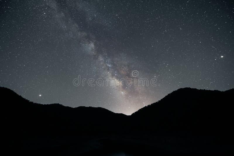 Nachtlandschap met kleurrijke Melkweg over Bergen stock foto's