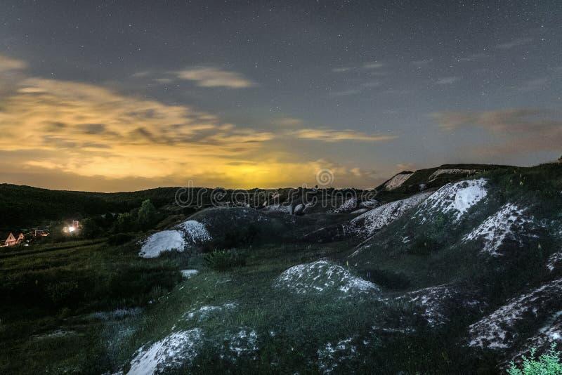 Nachtlandschap met krijtranden onder bewolkte en sterrige hemel stock fotografie