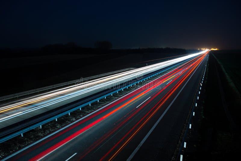 Nachtlandstraße mit Autoverkehr und undeutlichen Lichtern