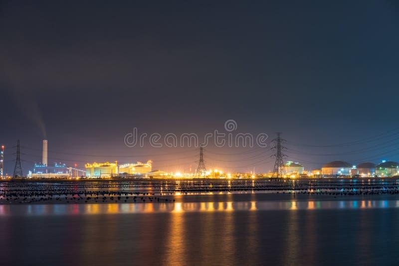 Nachtlicht bij de fabriek dichtbij de oceaan, de fabriek van de Olieraffinaderij, petrochemische installatie, Aardolie stock afbeeldingen