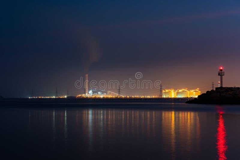 Nachtlicht an der Fabrik nahe dem Ozean, Erdölraffineriefabrik, petrochemisches Werk, Erdöl lizenzfreie stockfotos