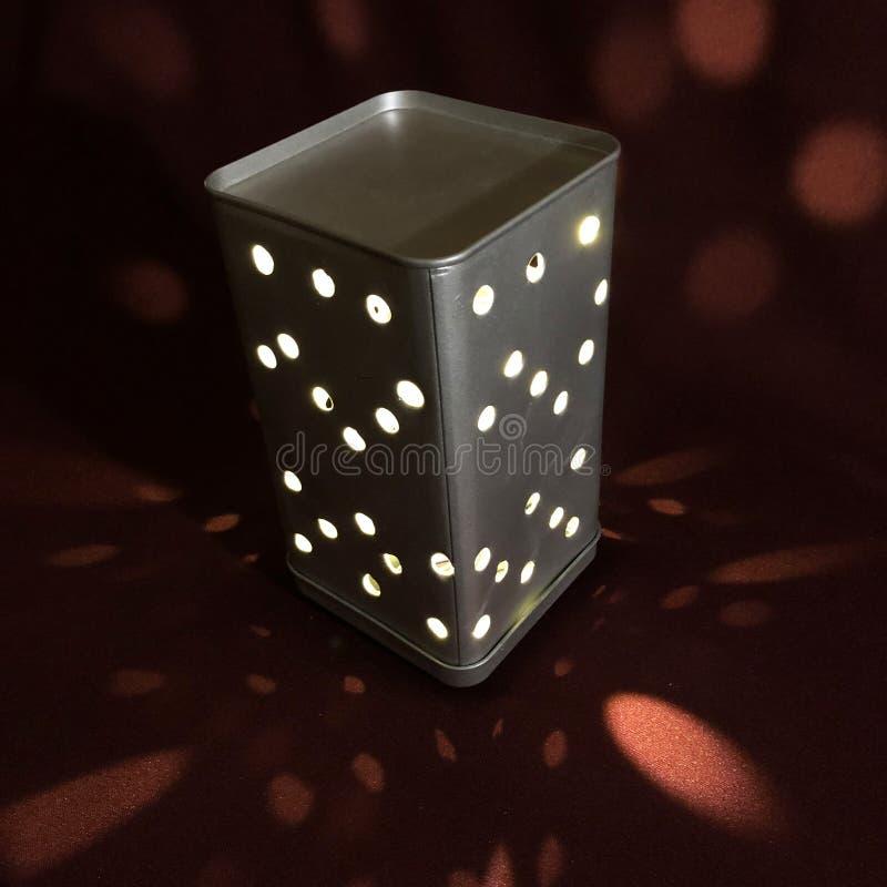 Nachtlicht in einem Metallkasten mit L?chern mit einem Burgunder-Hintergrund lizenzfreie stockfotografie