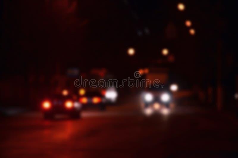 Nachtlichter der Großstadt, der unscharfen Nachtallee mit bokeh Ampeln und der Scheinwerfer des nähernden Autos lizenzfreies stockfoto