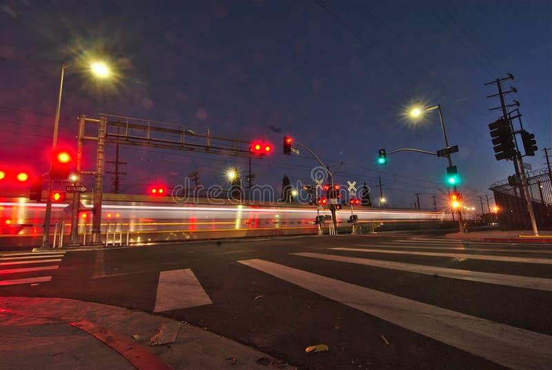 Nachtlichter eines Nahverkehrszugstreifens über einem Straßenschnitt nahe bei einem Zebrastreifen stockfotos