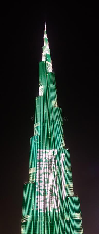 Nachtmening aan de wolkenkrabber van Burj Khalifa in Doubai, vlag van Saudi-Arabië, de V.A.E stock fotografie
