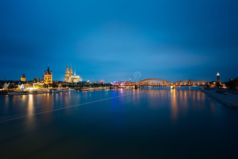 Nachtmening van de Kathedraal van Keulen en Hohenzollern-Brug, Duitsland stock foto's