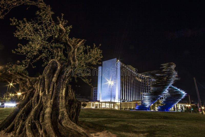 Nachtmening van het standbeeld van Hilton Athens, van Griekenland en van het glas stock afbeeldingen