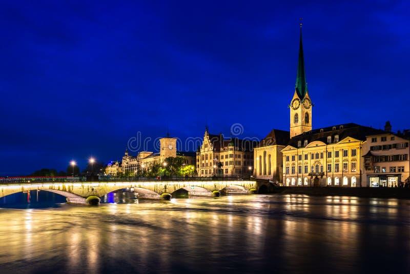 Nachtmening van historisch de stadscentrum van Zürich met beroemde Fraumunster-Kerk en rivier Limmat in Zürich, Zwitserland stock fotografie