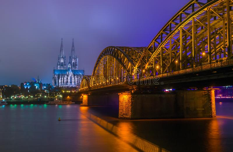 Nachtmening van Hohenzollern-Brug en de kathedraal in Keulen, Duitsland stock foto's