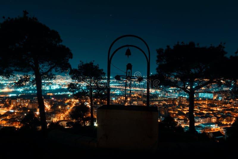 Nachtmening van over hoofdstad van Georgië, Tbilisi Straatlantaarns en heuvels die de stad omringen Blauw hemel en kerkkruis op b stock afbeelding