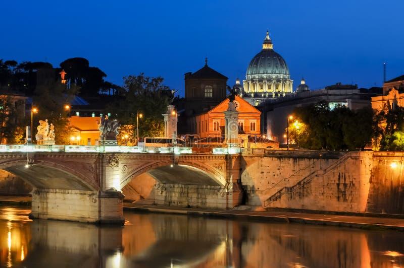 Nachtmening van Victor Emmanuel-brug over Tiber-rivier met St Peter ` s Kathedraalkoepel bij achtergrond, Rome, Italië royalty-vrije stock afbeelding
