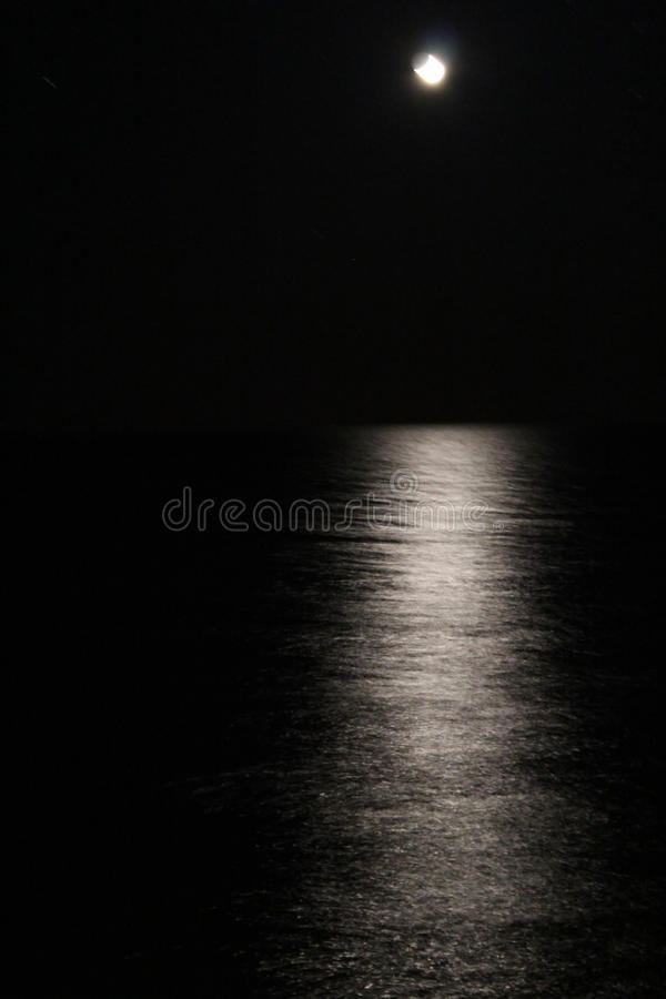 Nachtoverzees en de maan stock afbeelding