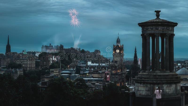 Nachtpanorama van de stad Edinburgh en vuurwerk stock fotografie