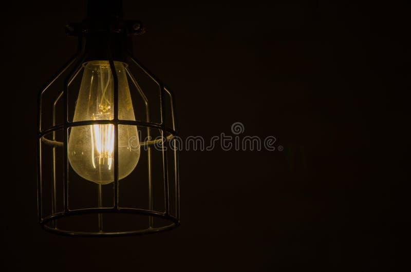Nachtphotographie der Glühlampe mit dem Metallkäfig lokalisiert auf schwarzem Hintergrund stockfoto